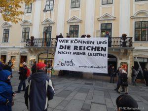 Aufbruch-Aktivist*innen besetzen kurzzeitig den Balkon der Casinos Austria und entrollen ein Transparent