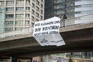 Aktivist*innen hängen ein Transparent von einer Brücke am Wiener Donaukanal.