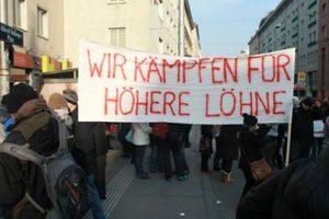 """Ein Transparent """"Wir kämpfen für höhere Löhne"""""""