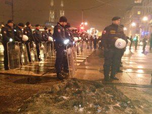 Mehrere Reihen Polizist*innen mit Schildern am Schottentor (Wien)